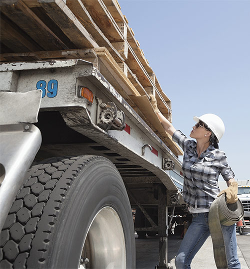 Female worker strapping down pallets on flatbed truck